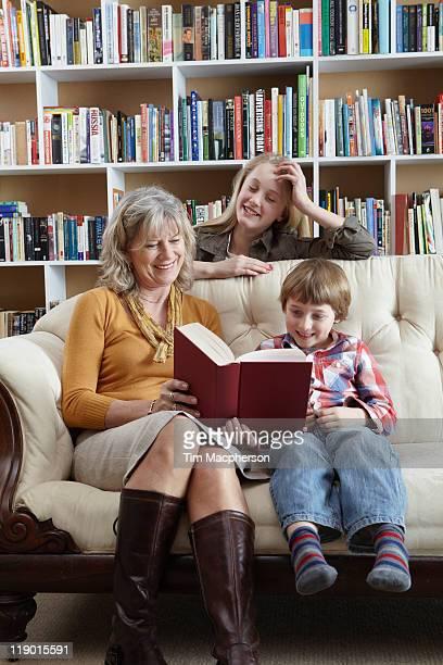 Femme lisant avec eux et petits-enfants