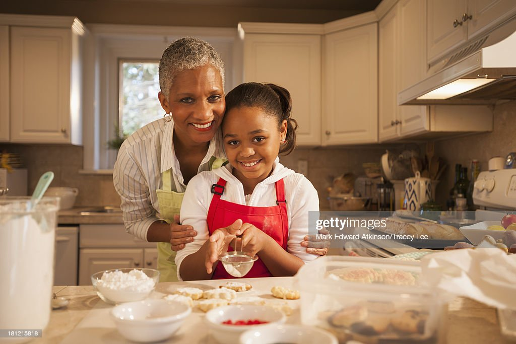 Woman and granddaughter baking in kitchen : Stock Photo