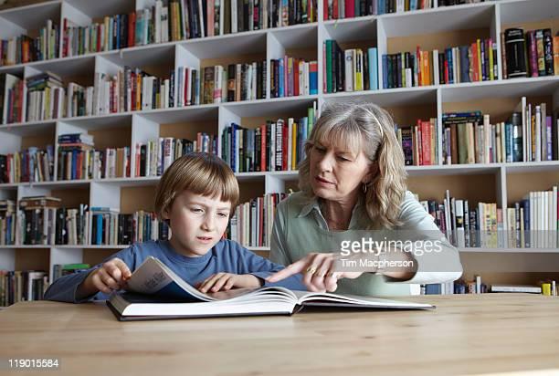 Femme et son petit-fils lire ensemble
