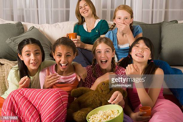 Woman and group of preteen girls watching tv