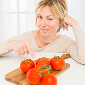 Smiling woman with tomatoes on plank winking at  the camera.
