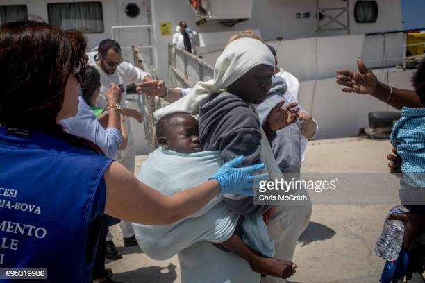 A woman and her baby are helped by volunteers as they disembark the Migrant Offshore Aid Station Phoenix vessel after arriving in port on June 12...