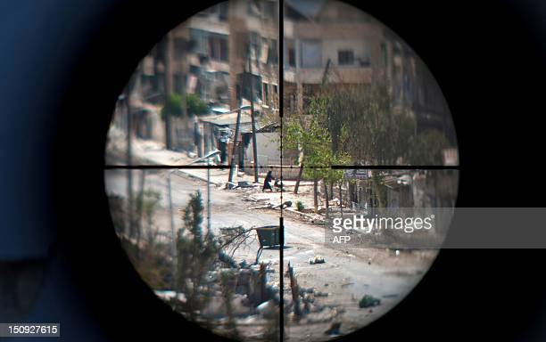 A woman and her baby are seen through the scope of an opposition fighter sniper gun as she flees the Saif alDawla neighbourhood of the Syrian...