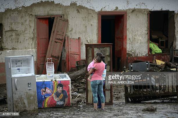 A woman and her baby remain outside their house after a landslide in Salgar Municipality Antioquia department Colombia on May 19 2015 A massive...