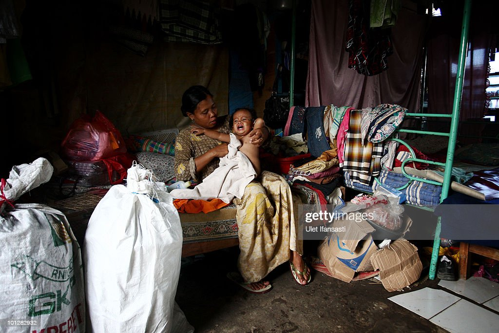 A woman and her baby sits inside their temporary home after her house was submerged by the mudflow from volcano 'Lusi' on May 30, 2010 in the subdistrict of Porong in Sidoarjo, East Java, Indonesia. Mud and gases continue to spew from Lusi four years after it first erupted, suspected to be triggered by the drilling activities of Indonesian oil and gas exploration company Lapindo Brantas. The initial eruption engulfed entire communities, wiping out villages and killing 13 people. Mud flow from the volcano continues at a rate of up to 150,000m3 per day, and to date has displaced tens of thousands of people.
