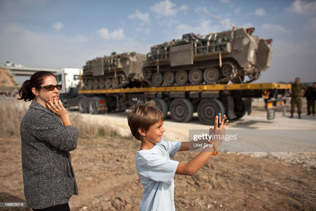A woman and her boy look at Israeli reserve soldiers and army vehicles as they depart the Gaza border area on November 22, 2012 near Israel's border with the Gaza Strip. The ceasefire between Israel and Hamas appears to be holding despite rockets being fired from Gaza. During the night the IDF reportedly arrested a number of 'terror operatives' in the West Bank in continued efforts to restore peace in the region.