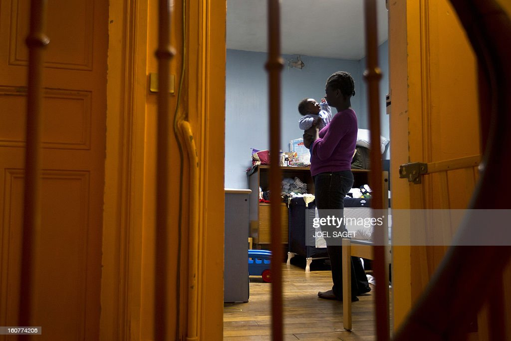 A woman and her child are seen in their room in an emergency shelter for homeless families administered by Catholic parishes on February 5, 2013 in Bondy, outside Paris.