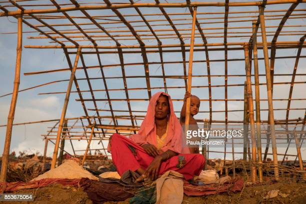 A woman and her child are seen inside a makeshift tent September 25 2017 in Thainkhali camp Cox's Bazar Bangladesh Over 429000 Rohingya refugees have...
