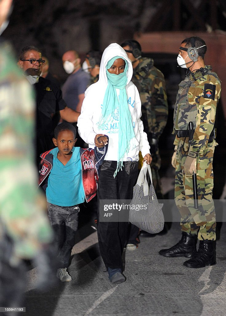 A woman and her child are shown to a waiting bus after arriving at the Armed forces of Malta Maritime base in Haywharf, on November 9, 2012 in Valletta. The Maltese military rescued 250 undocumented migrants believed to be Eritrean from a stricken boat, officials said, after reports the vessel had been adrift for days. AFP PHOTO/Matthew Mirabelli -MALTA