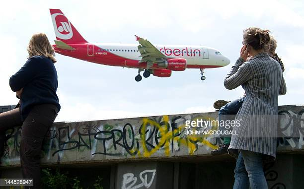 A woman and her child look at an Air Berlin aircraft as it lands at Berlin's Tegel airport May 15 2012 Air Berlin Germany's second largest airline...