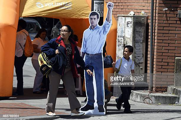 A woman and her child pass by a figure of jailed opposition leader Leopoldo Lopez gather during a demonstration in Caracas on February 18 2015...