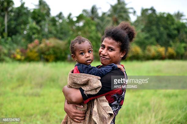 A woman and her child pose in the town of Kerema Papua New Guinea on September 7 2014 AFP PHOTO / ARIS MESSINIS