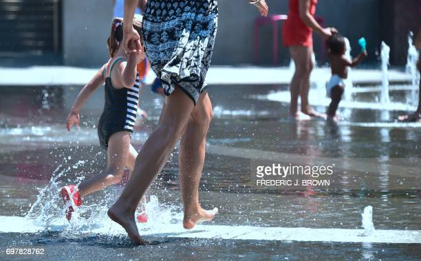 A woman and her child run through the shallow water at the Grand Park splash pad in downtown Los Angeles California on June 19 amid a Southern...
