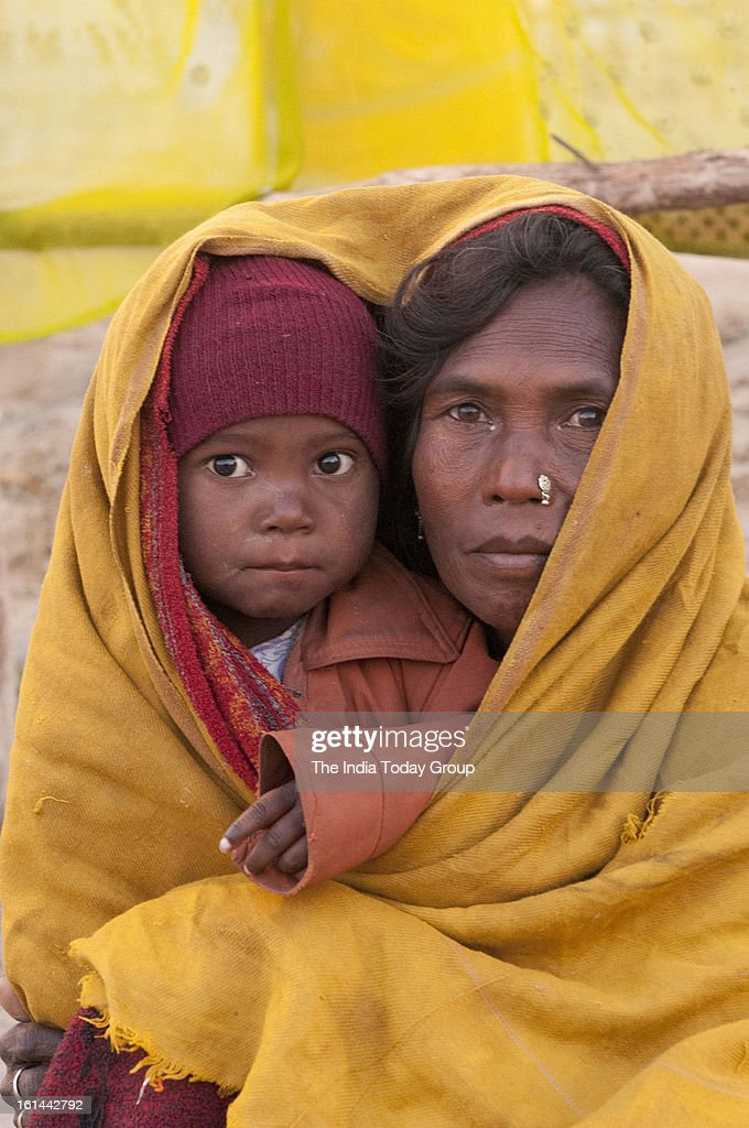 A woman and her child shelter from the early monring chill at the Sangam during the Mahakunbh Mela in Allahabad.