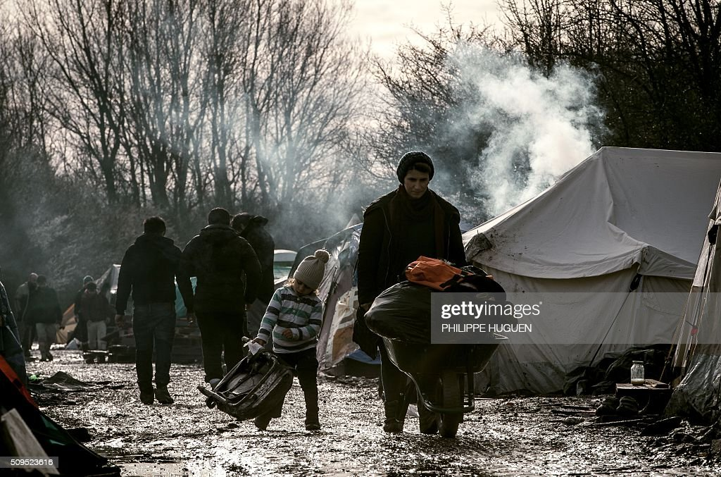 A woman and her child walk in the so-called 'Jungle' migrant camp in Gande-Synthe where 2,500 refugees from Kurdistan, Iraq and Syria live on February 11, 2016 in Grande-Synthe near the city of Dunkirk, northern France. / AFP / PHILIPPE HUGUEN