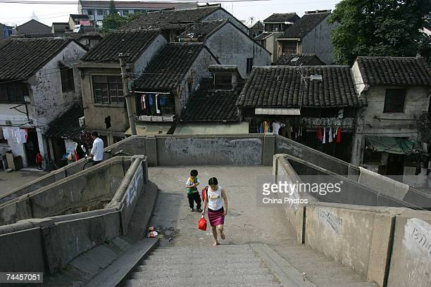 A woman and her child walk on the ancient Qingming Bridge June 8 2007 in Wuxi of Jiangsu Province China June 8 2007 in Wuxi of Jiangsu Province China...