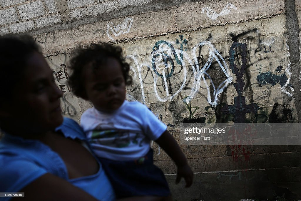 A woman and her child walk past gang graffiti in a neighborhood with heavy gang violence on July 20, 2012 in Tegucigalpa, Honduras. Honduras now has the highest per capita murder rate in the world and its capital city, Tegucigalpa, is plagued by violence, poverty, homelessness and sexual assaults. With an estimated 80% of the cocaine entering the United States now being trans-shipped through Honduras, the violence on the streets is a spillover from the ramped rise in narco-trafficking.
