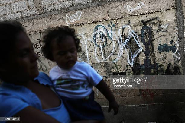 A woman and her child walk past gang graffiti in a neighborhood with heavy gang violence on July 20 2012 in Tegucigalpa Honduras Honduras now has the...