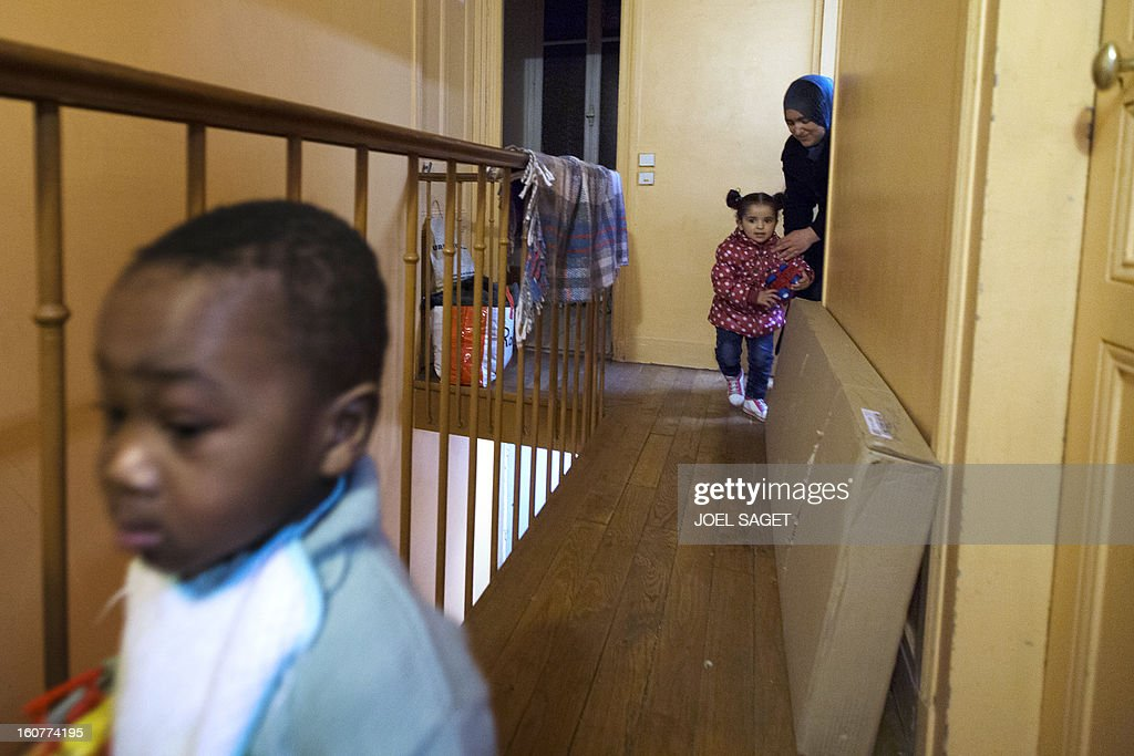 A woman and her children are seen in the corridor of an emergency shelter for homeless families administered by Catholic parishes on February 5, 2013 in Bondy, outside Paris.