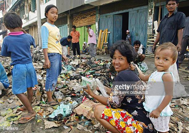 A woman and her children rumage through mudcaked rubbish in hopes of salvaging useful items two weeks after a tsunami hit the city of Meulaboh 09...