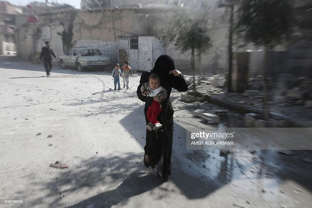 A woman and her children run for cover following reported air strikes by regime forces on the Kafr Batna town in the rebel-held Eastern Ghouta area, on the outskirts of the capital Damascus, on February 12, 2016. / AFP / AMER ALMOHIBANY