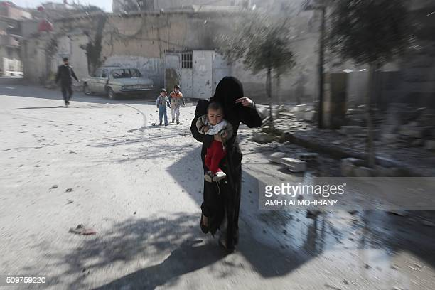 TOPSHOT A woman and her children run for cover following reported air strikes by regime forces on the Kafr Batna town in the rebelheld Eastern Ghouta...