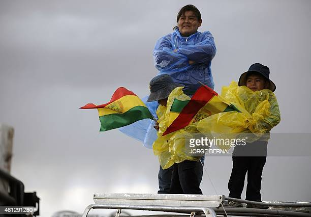A woman and her children stand atop a car to attend the Stage 7 of the Dakar 2015 between Iquique in Chile and Uyuni in Bolivia on January 10 2015...
