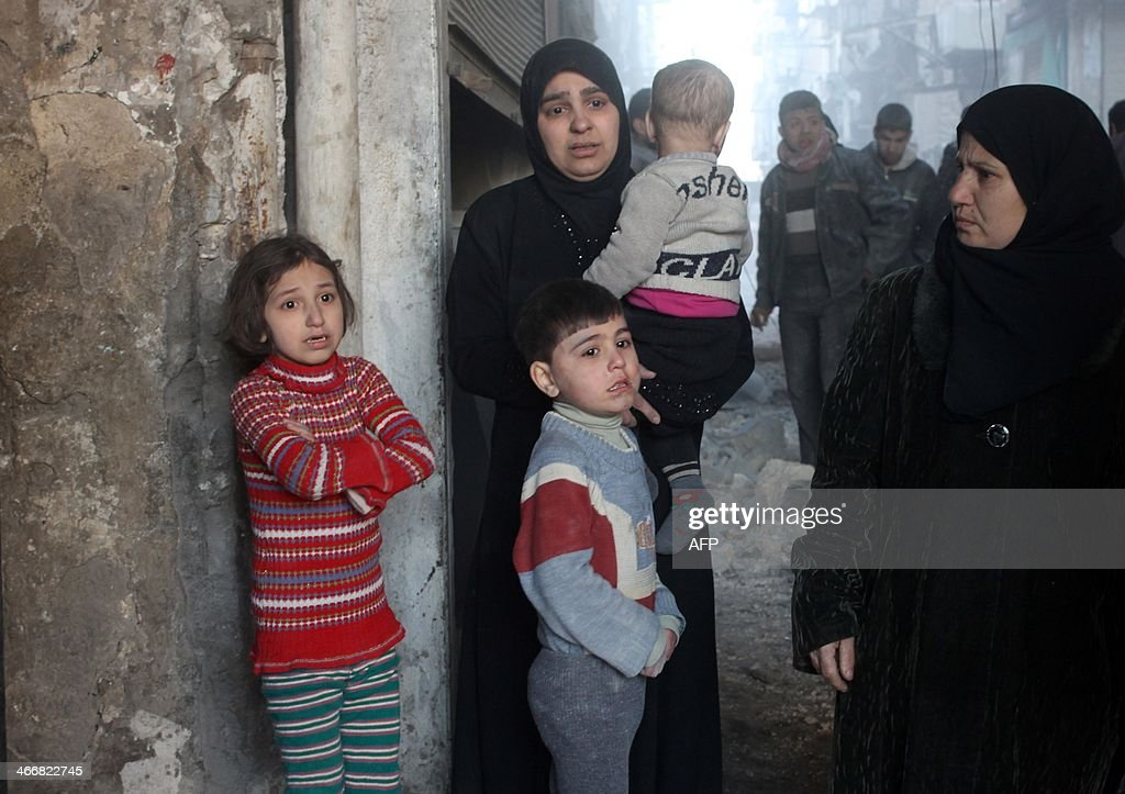 A woman and her children stand scared outside their home following a reported Syrian government forces air strike in the northern city of Aleppo on February 4, 2014. Syria's second city and onetime commercial hub has been divided since a major rebel offensive in the summer of 2012, and much of the city's historic Old Town has been demolished in the fighting.