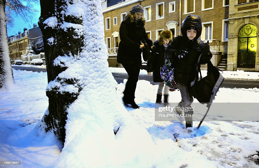 A woman and her children walk carefully on the way to the school on the sidewalk covered with fresh snow on January 15, 2013 in Arras, northern France, after snow blanketed several French departments. Road traffic is affected by snowfalls in northern and eastern regions.