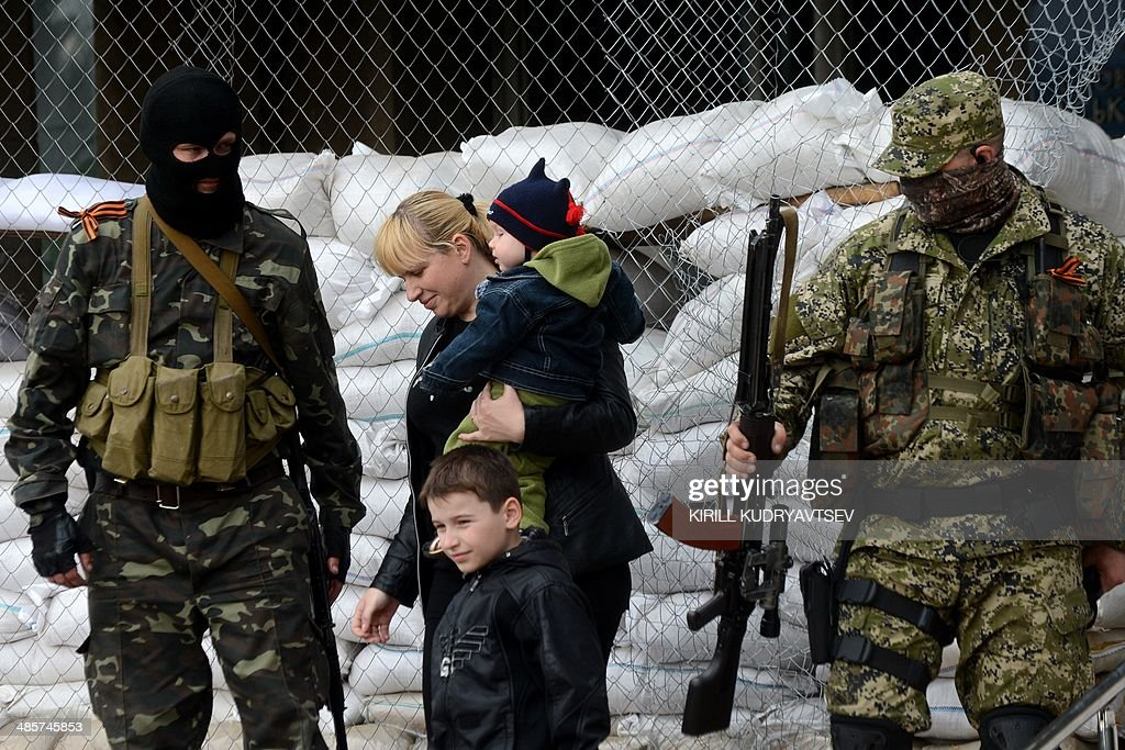 A woman and her children walk past armed men in military fatigues guarding a barricade outside the regional administration building in the eastern Ukrainian city of Slavyansk on April 20, 2014. Pro-Moscow rebels in Slavyansk declared a curfew there Sunday, after a gun battle with unidentified attackers killed two militants. Separatist rebels leader Vyacheslav Ponomaryov told reporters that 'the curfew comes into effect today'.