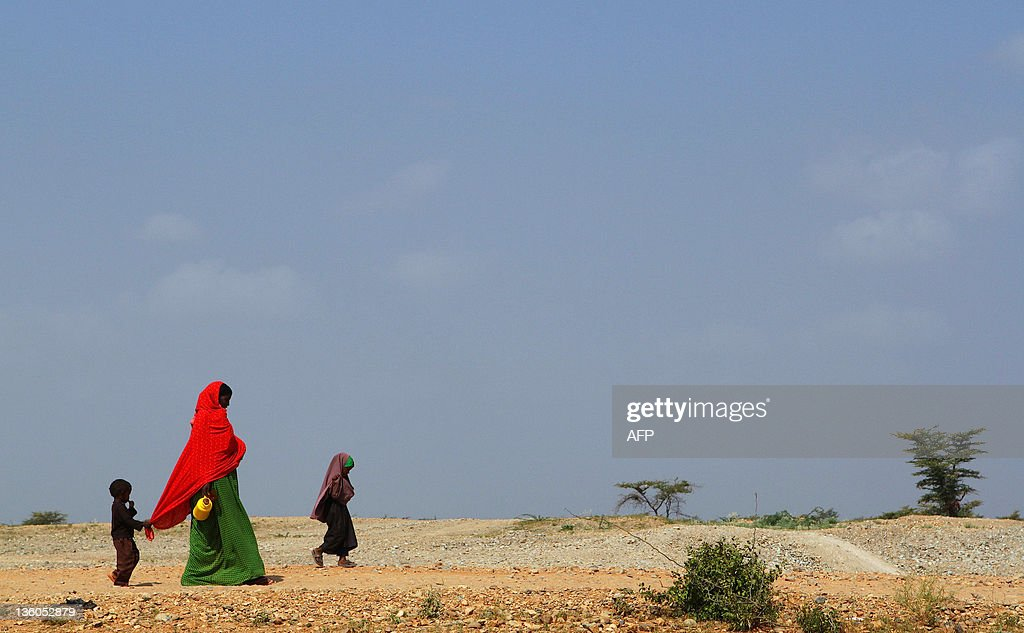 A woman and her children walk to the Transit Centre to find water in Dolo Ado Ethiopia on December 15 2011 Over 300000 refugees have fled severe...