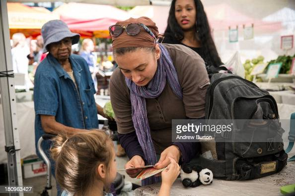 A woman and her daughter counts out Electronic Benefits Transfer coupons more commonly known as Food Stamps while shoping for groceries in the...