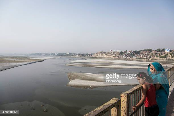 A woman and her daughter look out at the Ganges river from a bridge in Kanpur Uttar Pradesh India on Sunday May 31 2015 India plans to order 80...