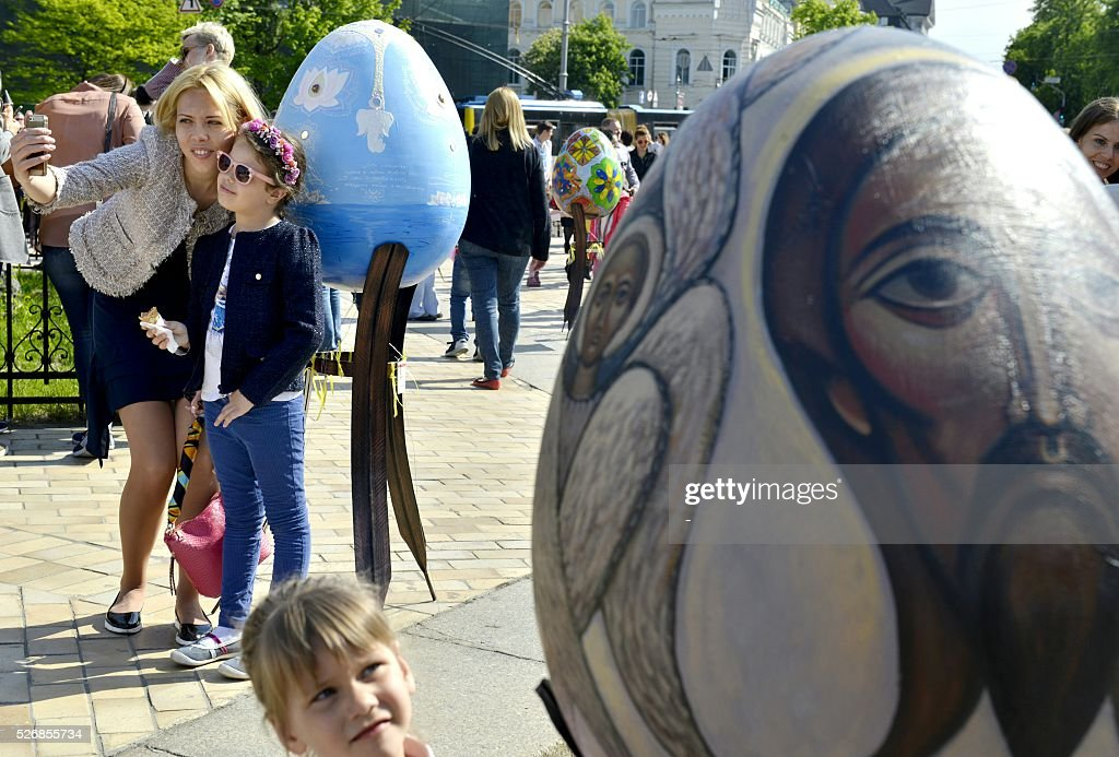 A woman and her daughter pose near a huge 'Pysanka', a traditional Easter egg, during the celebrations of Orthodox Easter as part of the Pysanka festival in Kiev on May 1, 2016. 374 huge eggs and 40 000 small ones decorated by Ukrainian artists are displayed at St. Sophiya square in Kiev. / AFP / -