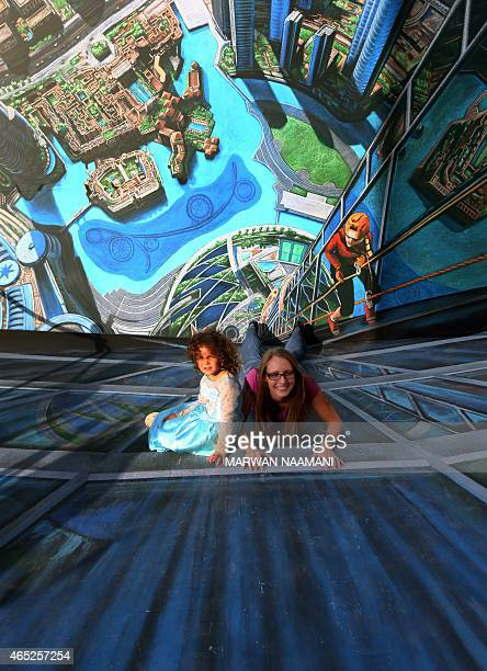 A woman and her daughter pose on a chalk 3D artwork on March 4 2015 near the Jumeirah Beach Residence in Dubai during the Canvas Festival a...
