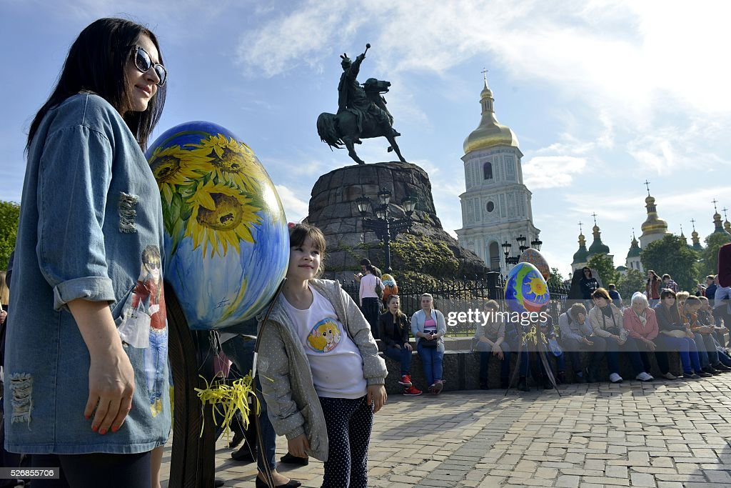 A woman and her daughter poses near a huge 'Pysanka', a traditional Easter egg, during the celebrations of Orthodox Easter as part of the Pysanka festival in Kiev on May 1, 2016. 374 huge eggs and 40 000 small ones decorated by Ukrainian artists are displayed at St. Sophiya square in Kiev. / AFP / -