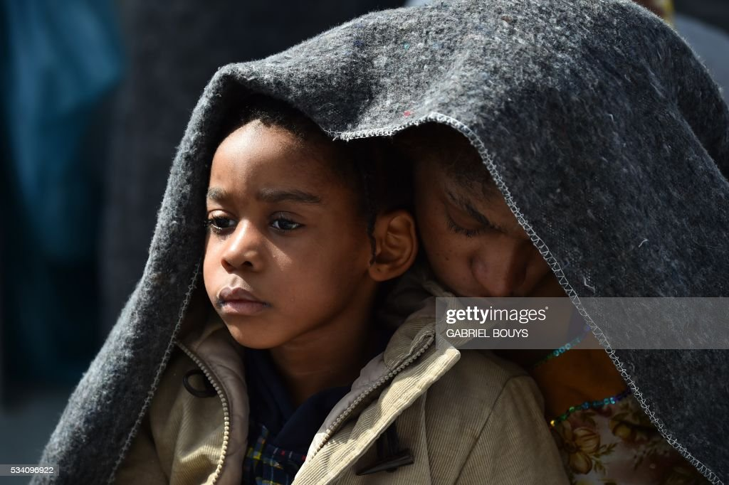 A woman and her daughter protect themselves with a blanket aboard the rescue ship 'Aquarius', on May 25, 2016 a day after a rescue operation of migrants and refugees off the Libyan coast. The Aquarius is a former North Atlantic fisheries protection ship now used by humanitarians SOS Mediterranee and Medecins Sans Frontieres (Doctors without Borders) which patrols to rescue migrants and refugees trying to reach Europe crossing the Mediterranean sea aboard rubber boats or old fishing boat. / AFP / GABRIEL