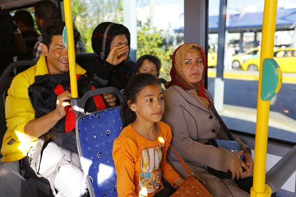 A woman and her daughter sit in a bus that will bring them...
