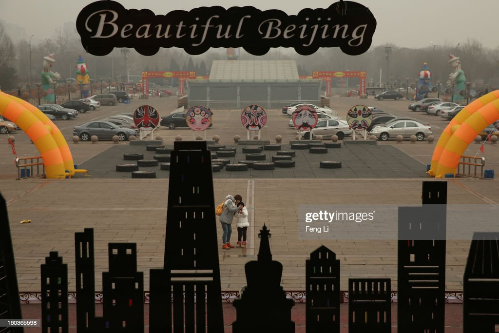 A woman and her daughter take photos near the billboard with Beijing's landmark building during severe pollution on January 30, 2013 in Beijing, China. The fourth round of heavy smog to hit Beijing in one month has sent more people to the hospital with respiratory illnesses and prompted calls for legislation to curb pollution. The haze choking many Chinese cities covers a total area of 1.3 million square kilometers, the China's Ministry of Environmental Protection said Tuesday.