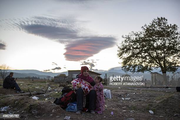 A woman and her daughter wait along with other migrants and refugees to enter a registration camp after crossing the GreekMacedonian border near...