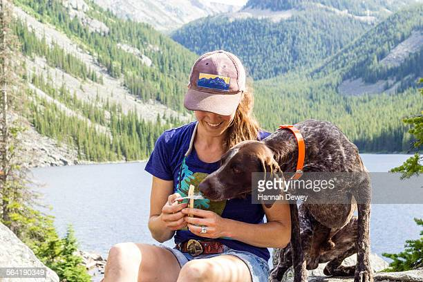 Woman and her dog have a snack while hiking