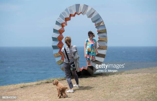 A woman and her dog take a photo of a friend beside 'Foci' by Karl Meyer at Sculpture By The Sea on October 18 2017 in Sydney Australia The annual...
