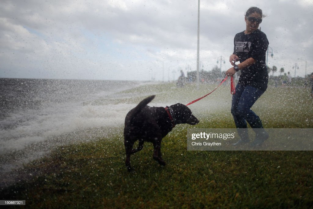A woman and her dog watch the waves on the shore of Lake Pontchartrain from Hurricane Isaac on August 28, 2012 in New Orleans, Louisiana. Hurricane Isaac is expected to make landfall later tonight along the Louisiana coast