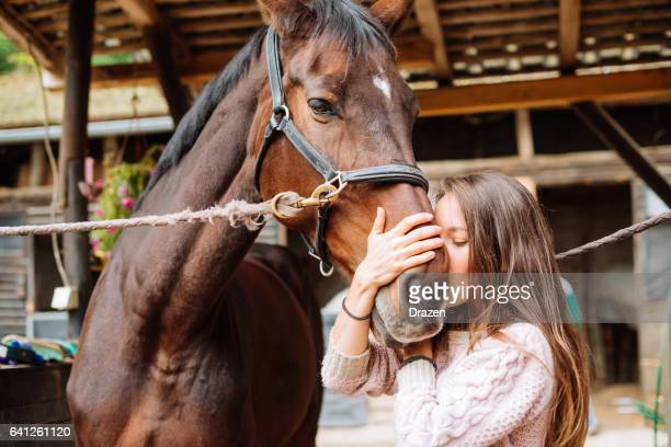 Woman and her horse in stable, cleaning, brushing and getting ready for dressage
