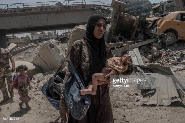 A woman and her sick child flee as Iraqi Army soldiers fight Islamic State militants who occupy the last section of the Old City district on July 10...