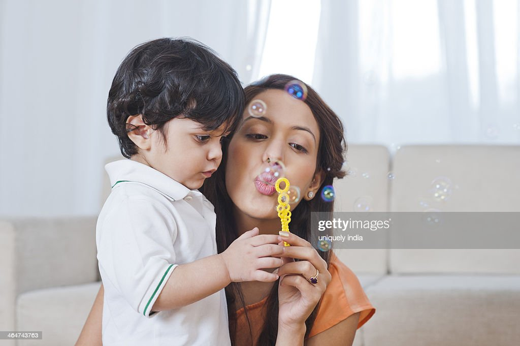Woman and her son blowing bubbles with a bubble : Stock Photo