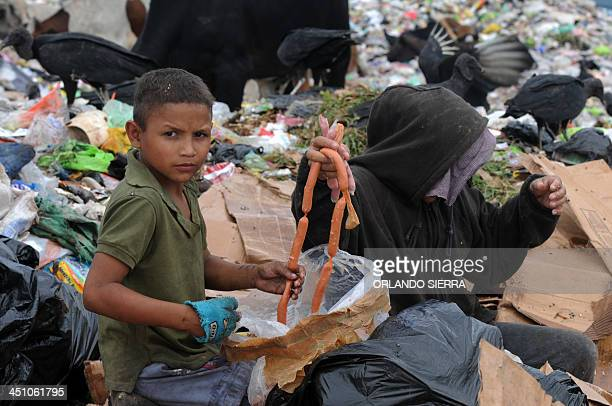 A woman and her son collect food from the garbage at the municipal rubbish dump 20 km north of Tegucigalpa on November 21 2013 Honduras one of the...