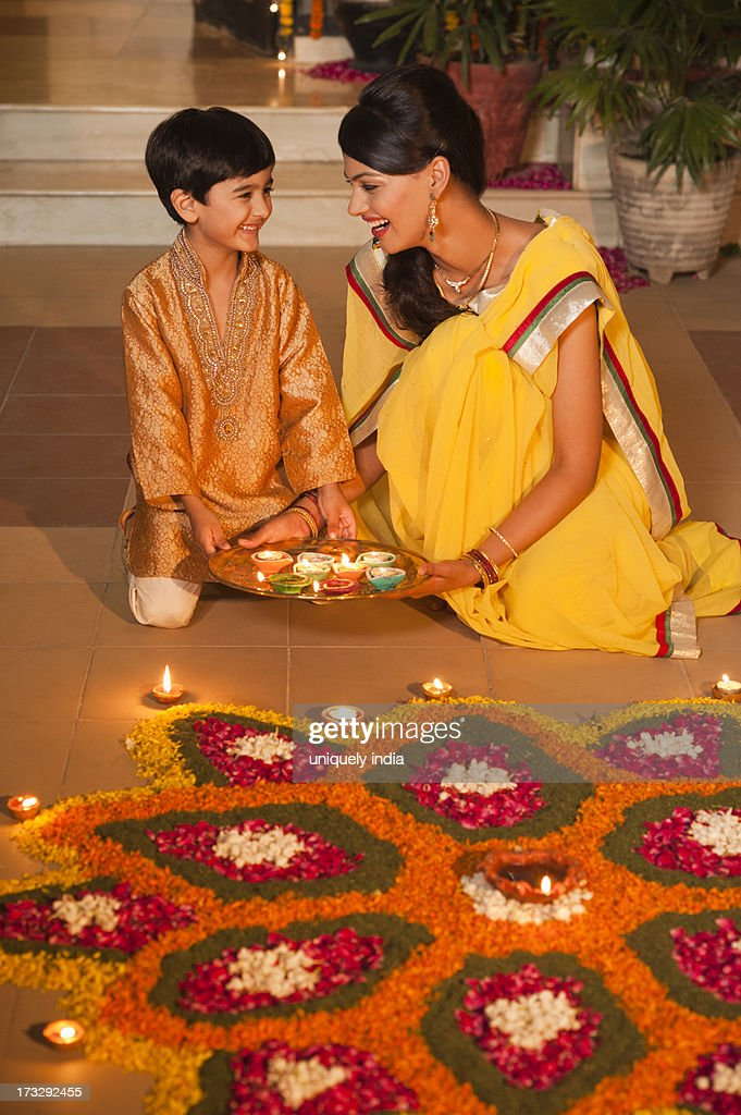 Woman and her son decorating rangoli with oil lamps on Diwali