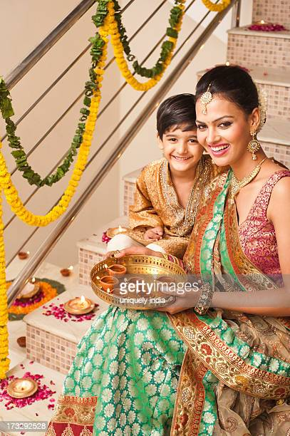 Woman and her son decorating with oil lamps on Diwali