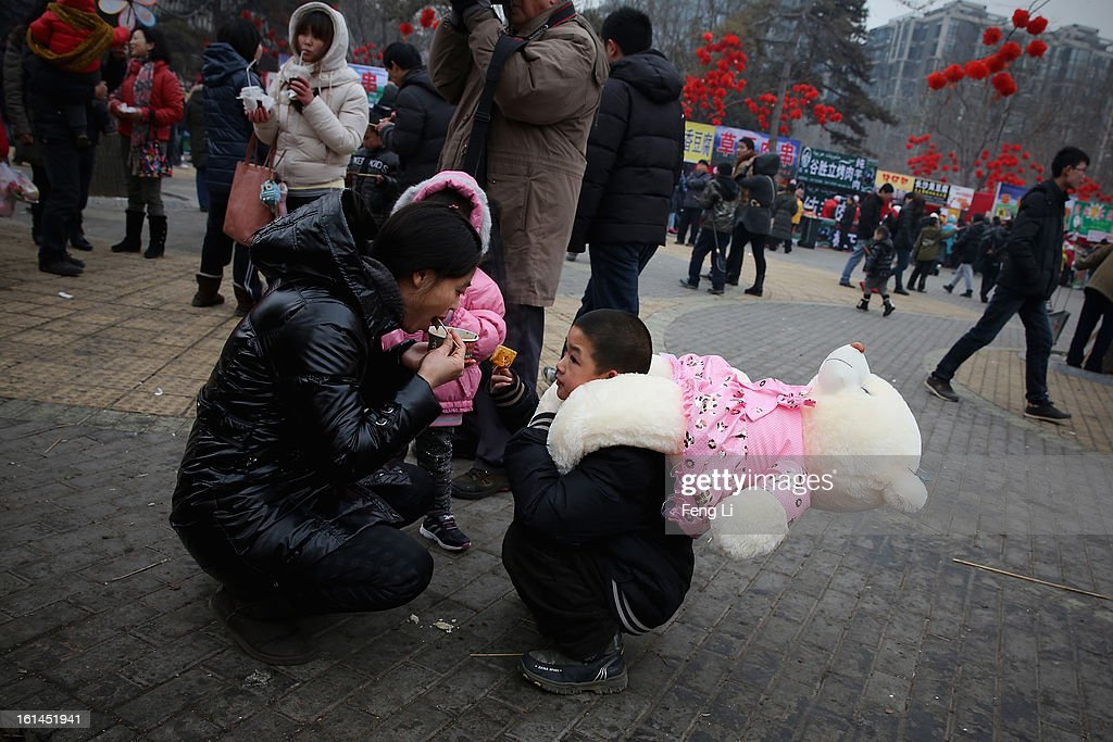 A woman and her son eat bean curd at a Spring Festival Temple Fair for celebrating Chinese Lunar New Year of Snake on February 11, 2013 in Beijing, China. The Chinese Lunar New Year of Snake also known as the Spring Festival, which is based on the Lunisolar Chinese calendar, is celebrated from the first day of the first month of the lunar year and ends with Lantern Festival on the Fifteenth day.